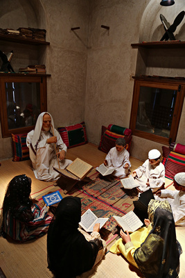 A diorama depicting boys and girls being instructed in the Koran