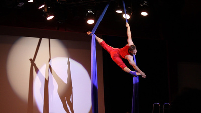 Lance Ringnald doing an acrobatic performance using hanging silks