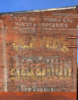 Faded signs on brick building in Chinatown