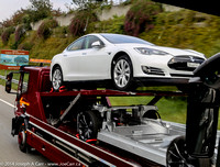 White Tesla Model S and spare chassis on a transport truck