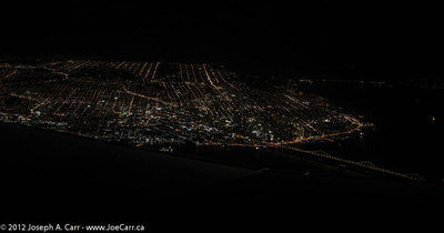 San Francisco lights at night with Bay Bridge from the aircraft