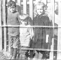 George, Harry & Hilda Carruthers standing in front of a fence