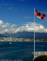Seabus ferry & the North Shore and the Canadian flag on the prow of Canada Place