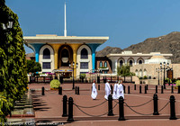 Omani men walk across the front courtyard of the Sultan's palace