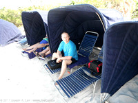 Joe in a lounge chair under a clamshell on the beach