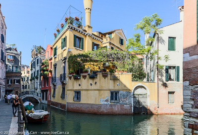 Canal intersection with patios and homes above in Venice