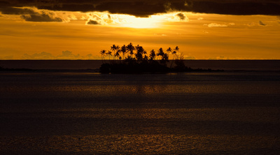 Sunset south of Bora Bora with palm trees on a motu from the westerly shore of Taha'a
