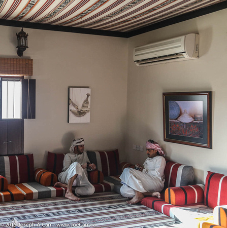 Two young Omani men recline in the lobby