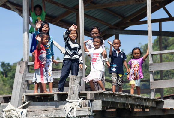 Kids waving at us from the Malay stilt village