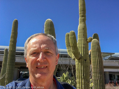 JoeTourist: Tucson &emdash; Joe's selfie in front of some Saguero cactus outside the airport entrance