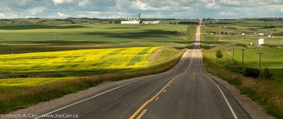 A long and straight prairie road through Prairie farm fields