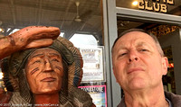Joe hamming it up beside a wooden indian on the street