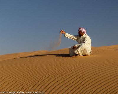 JoeTourist: Liwa Oasis &emdash; Arab man sitting on a sand dune